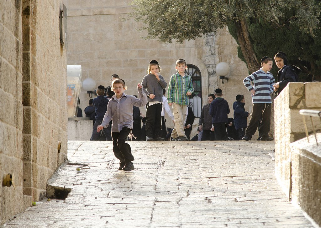Pupils in streets of Jerusalem, sliding on wet floor