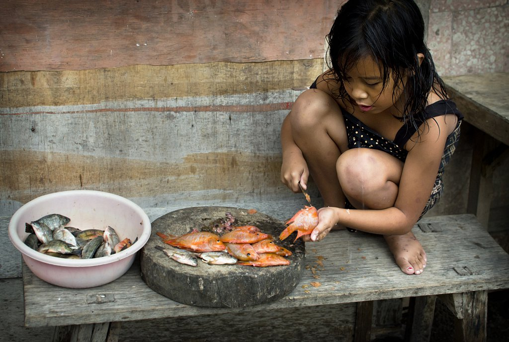 Girl cutting fish in Trunyan